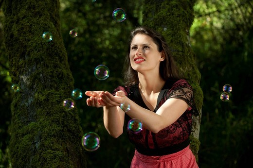 Caucasian woman trying to catch bubbles in her hands : Stock Photo