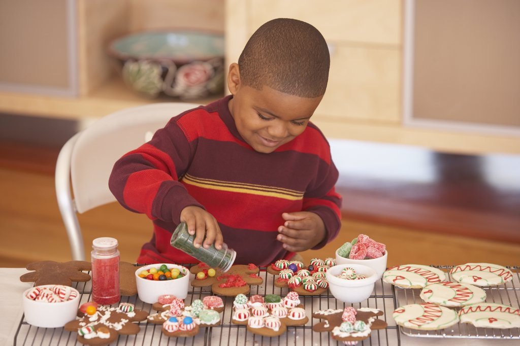 Stock Photo: 1589R-13954 Young boy making gingerbread men