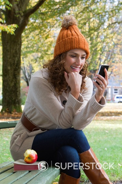 Stock Photo: 1589R-139543 Hispanic woman using cell phone in park