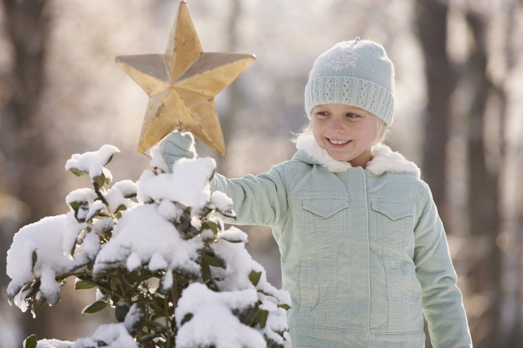 Young girl decorating a snowy Christmas tree with a star : Stock Photo