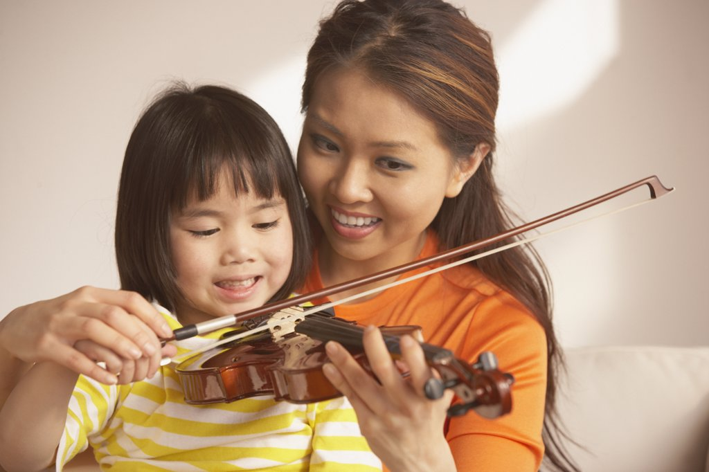 Mother helping her daughter play the violin : Stock Photo