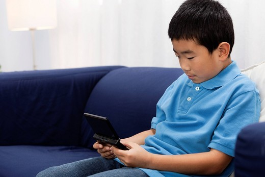 Korean boy playing video game : Stock Photo