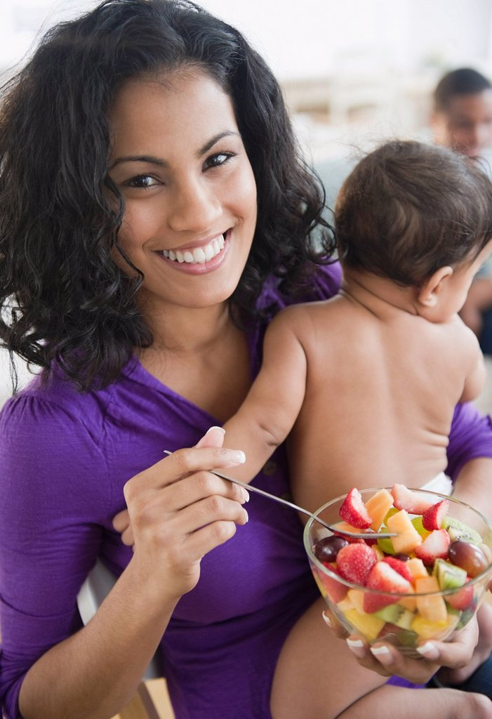 Mother holding baby and eating fruit salad : Stock Photo