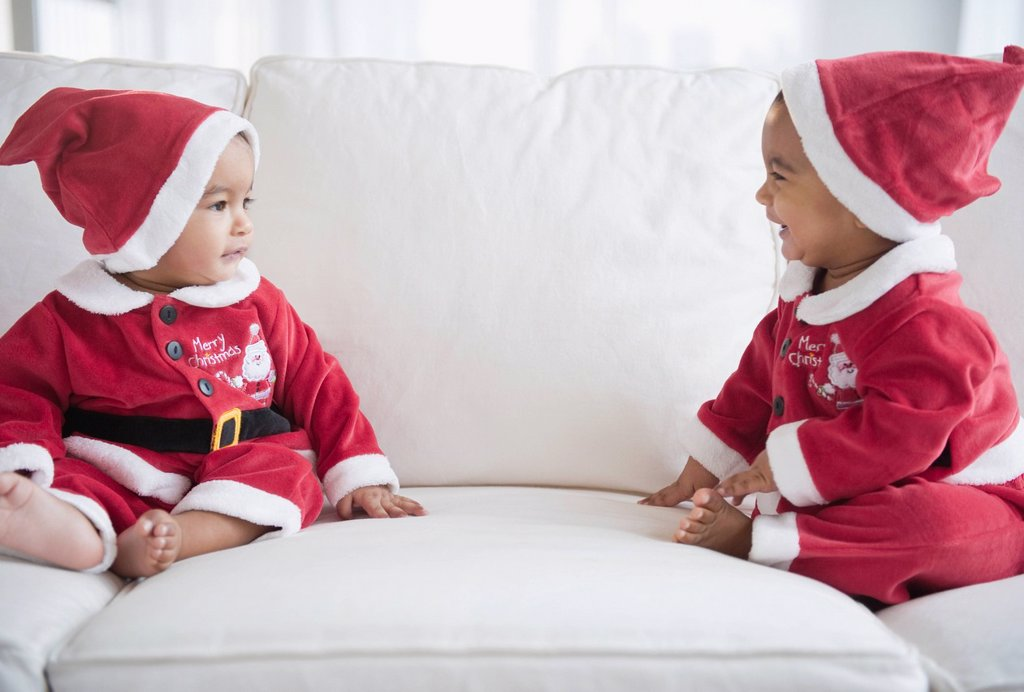 Stock Photo: 1589R-140104 Twins on sofa dressed in Santa outfits