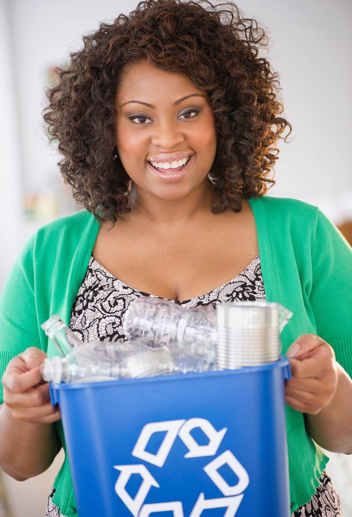 African American woman carrying recycling bin : Stock Photo