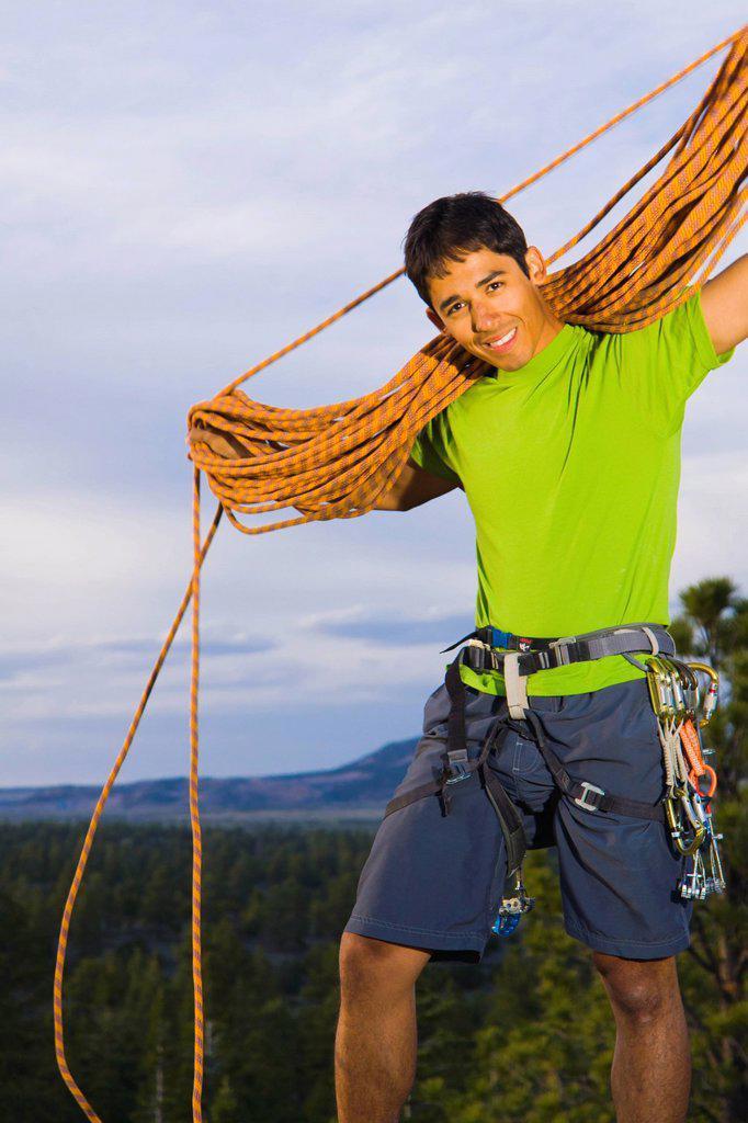 Stock Photo: 1589R-140217 Hispanic man preparing for rock climbing