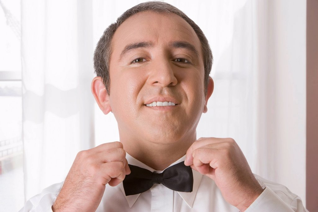 Hispanic man tying bow tie : Stock Photo