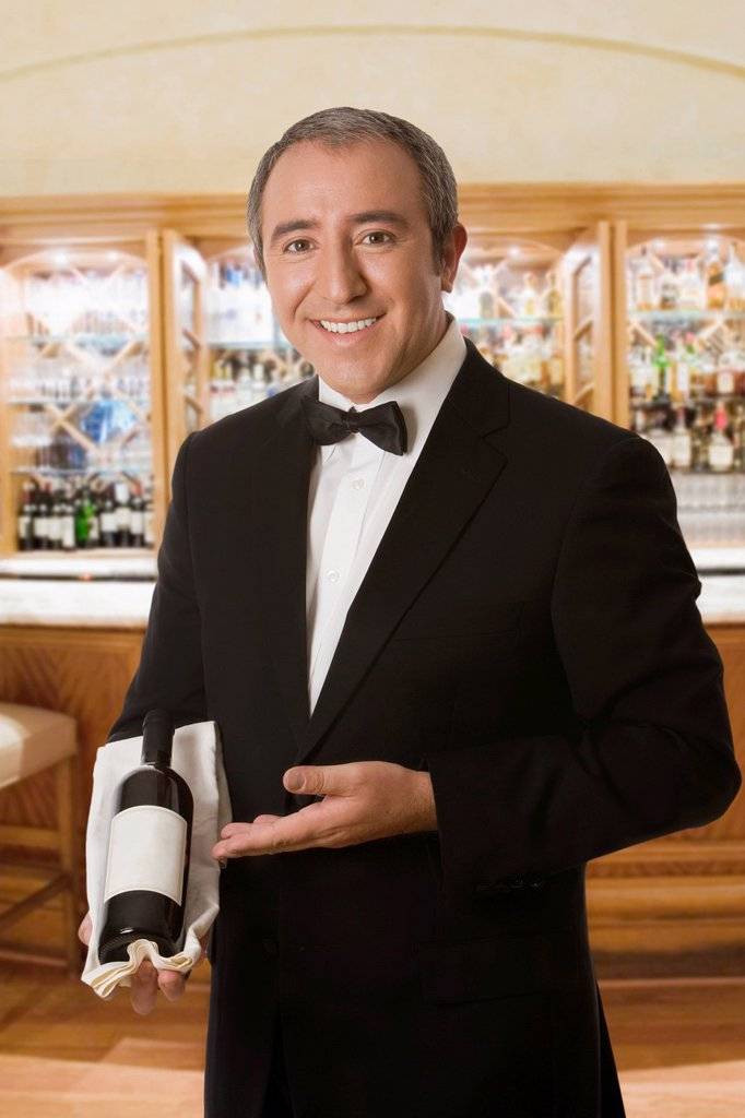 Hispanic sommelier displaying a bottle of wine : Stock Photo
