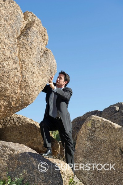 Stock Photo: 1589R-140377 Caucasian businessman pushing large rock