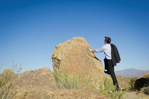 Caucasian businessman standing near rock : Stock Photo