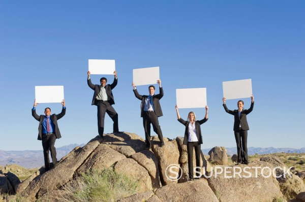 Stock Photo: 1589R-140390 Business people standing on rocks holding placards