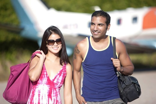 Couple on vacation leaving airplane : Stock Photo