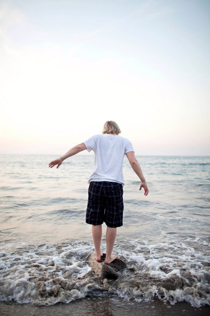 Caucasian woman standing on rock in ocean : Stock Photo