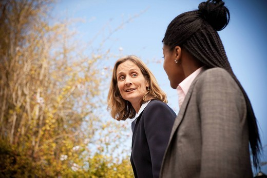 Businesswomen walking together outdoors : Stock Photo