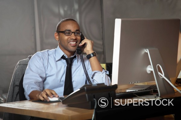 Stock Photo: 1589R-140800 African American businessman working at desk and talking on telephone