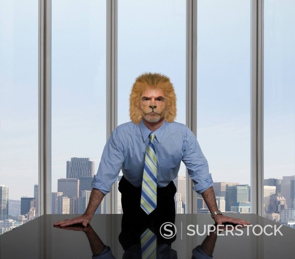 Businessman with lion´s head leaning on table : Stock Photo