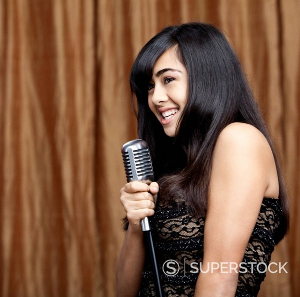 Filipino teenage girl singing into microphone : Stock Photo