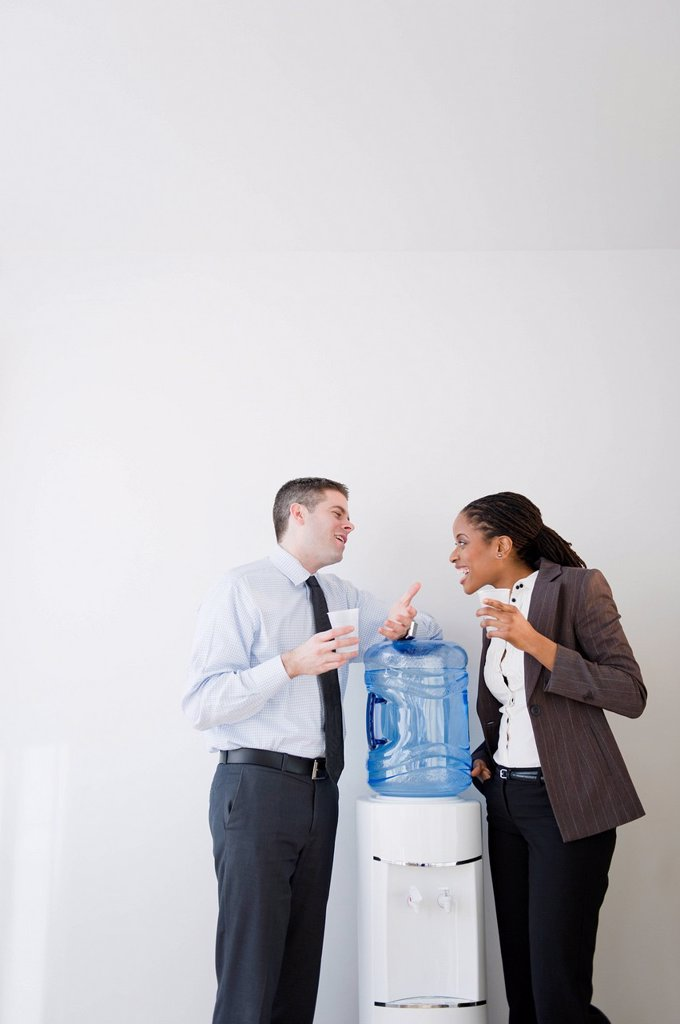 Business people talking together at water cooler : Stock Photo