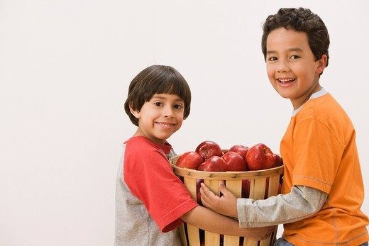 Hispanic brothers carrying basket of apples : Stock Photo