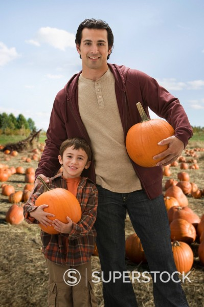 Caucasian father and son holding pumpkins in pumpkin patch : Stock Photo