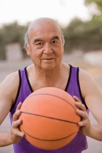 Senior Chilean man playing basketball : Stock Photo