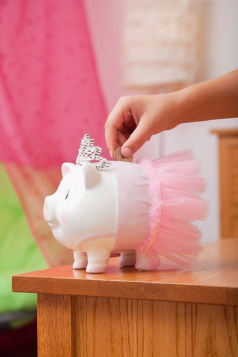 African American girl putting coin into piggy bank : Stock Photo