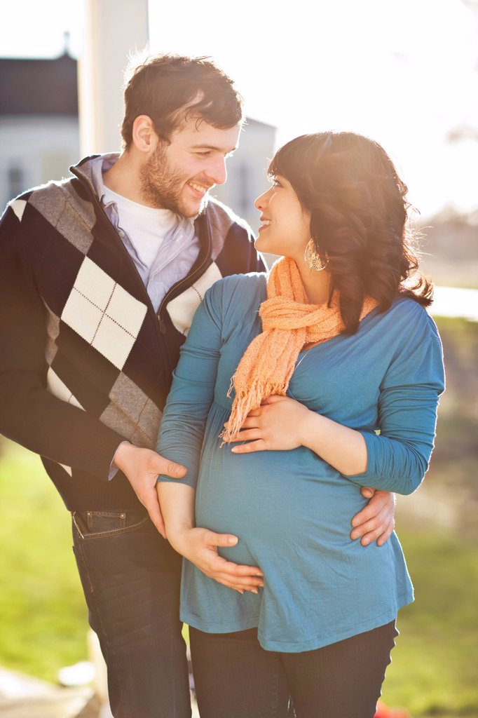 Stock Photo: 1589R-141862 Husband hugging pregnant wife
