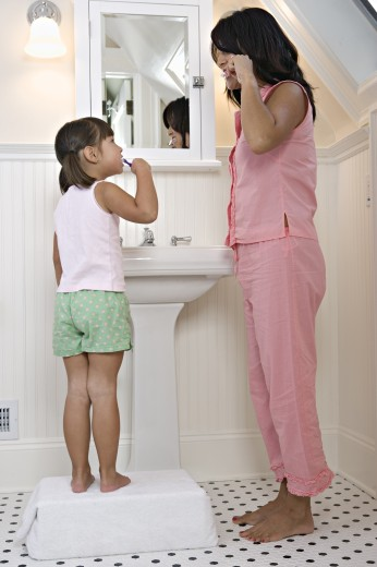 Stock Photo: 1589R-14297 Mom and daughter brushing teeth