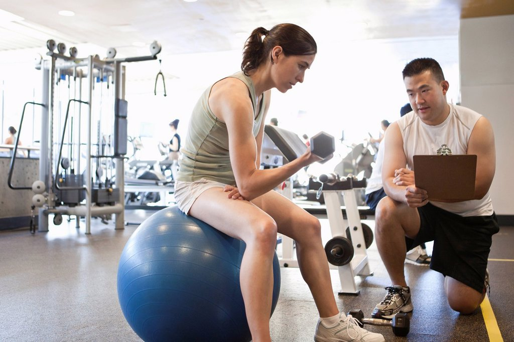Stock Photo: 1589R-143714 Woman working with personal trainer in health club