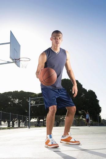 Mixed race man playing basketball : Stock Photo