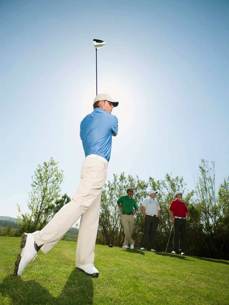 Men playing golf together on golf course : Stock Photo