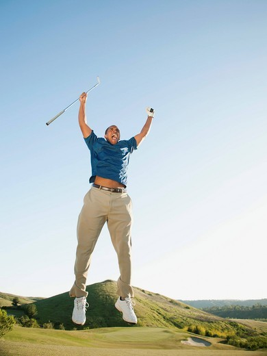Excited Black golfer jumping in mid_air on golf course : Stock Photo