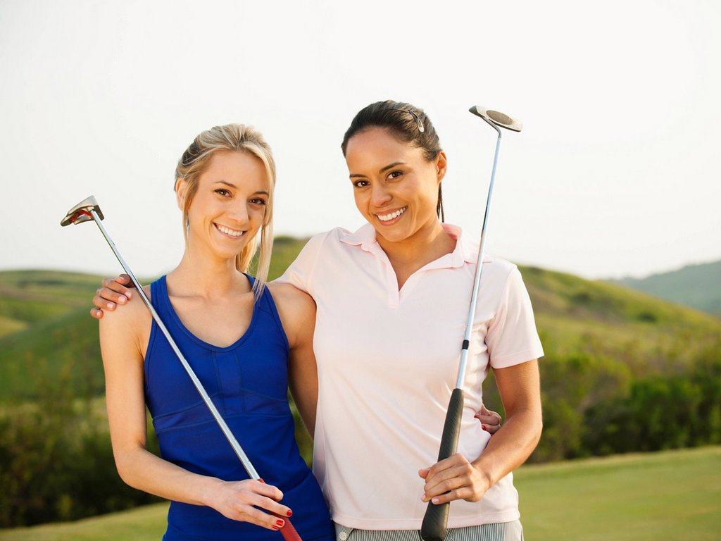 Stock Photo: 1589R-143918 Women with golf clubs hugging on golf course