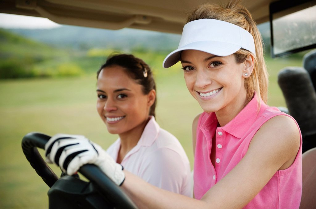Stock Photo: 1589R-143924 Women driving golf cart on golf course