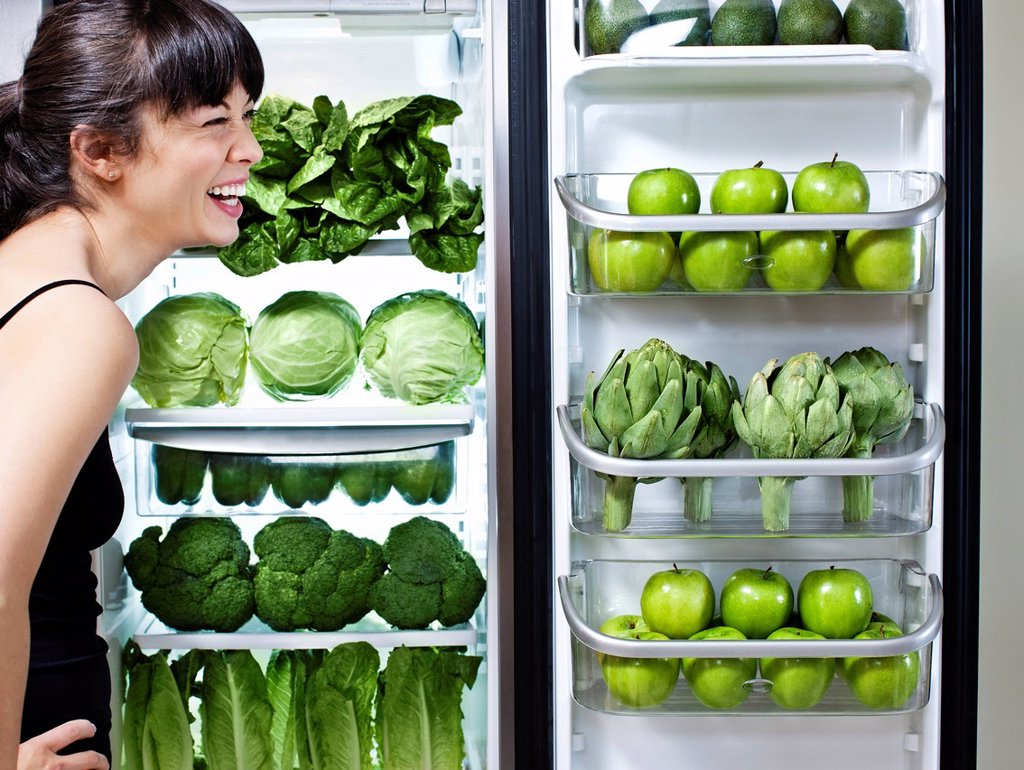 Stock Photo: 1589R-143951 Mixed race woman looking at green vegetables in refrigerator