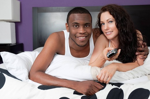 Couple laying in bed watching television together : Stock Photo