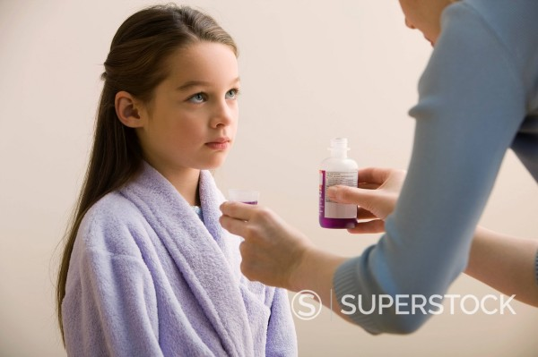 Stock Photo: 1589R-144111 Mother giving daughter cough medicine