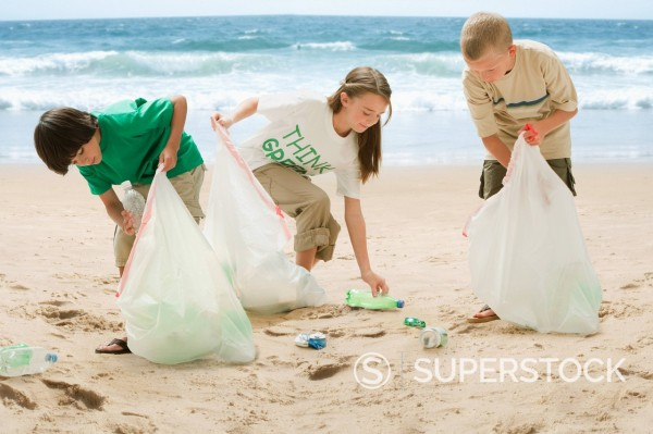 Caucasian children picking up litter from beach : Stock Photo