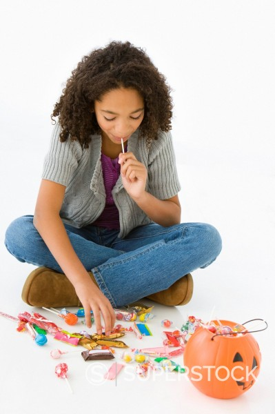 Stock Photo: 1589R-144173 Mixed race girl eating Halloween candy