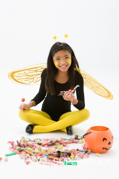 Asian girl in bee costume eating Halloween candy : Stock Photo