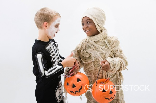 Stock Photo: 1589R-144220 Boys in skeleton and mummy costumes trading Halloween candy