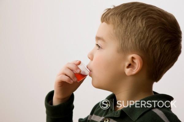 Stock Photo: 1589R-144285 Caucasian boy taking cough medicine