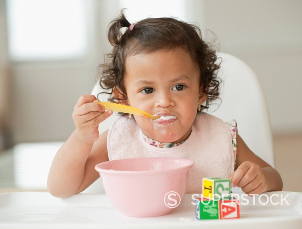 Stock Photo: 1589R-144451 Hispanic girl eating in high chair