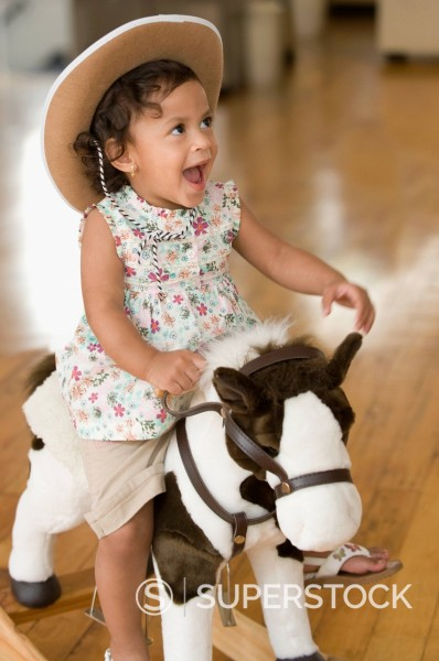Stock Photo: 1589R-144472 Hispanic girl riding toy horse and wearing cowboy hat