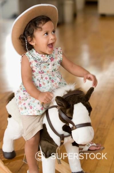 Hispanic girl riding toy horse and wearing cowboy hat : Stock Photo