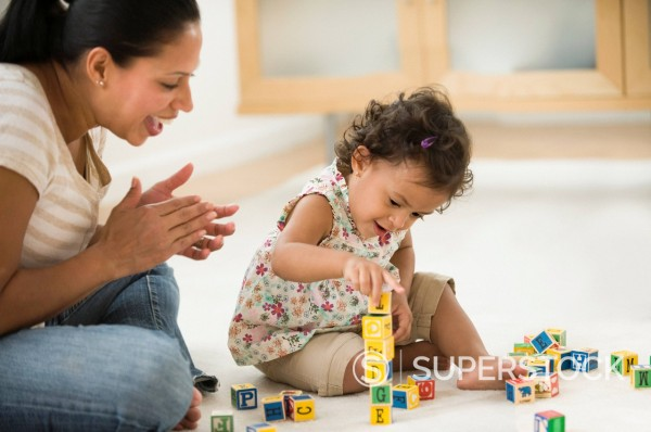 Hispanic mother watching daughter playing with alphabet blocks : Stock Photo