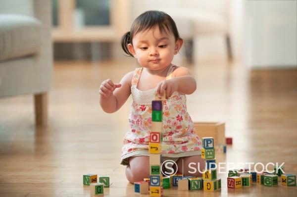Hispanic girl sitting on floor playing with alphabet blocks : Stock Photo