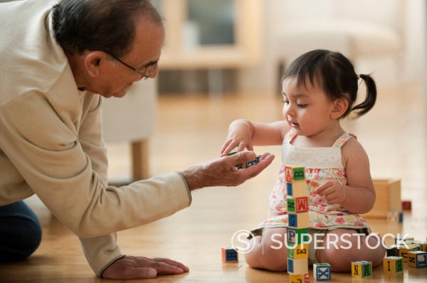 Stock Photo: 1589R-144511 Hispanic grandfather and granddaughter playing with alphabet blocks