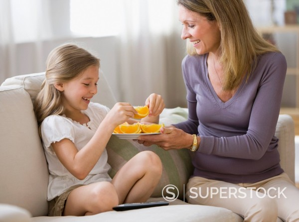 Stock Photo: 1589R-144543 Caucasian mother offering orange slices to daughter