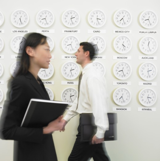 Stock Photo: 1589R-14466 Businessman and businesswoman walking with time zone clocks on the wall behind them